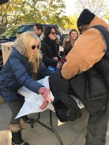 Jodie Gross of Franklin assists in distributing a new winter coat, one of 100 coats distributed.